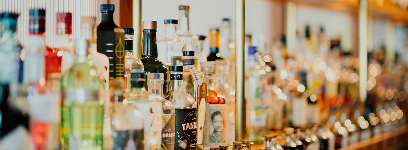 Several bottles of alcohol on a shelf and can be a cause of impotence for men.